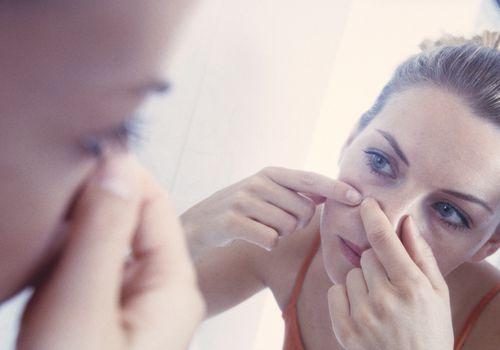 Woman examining pimple