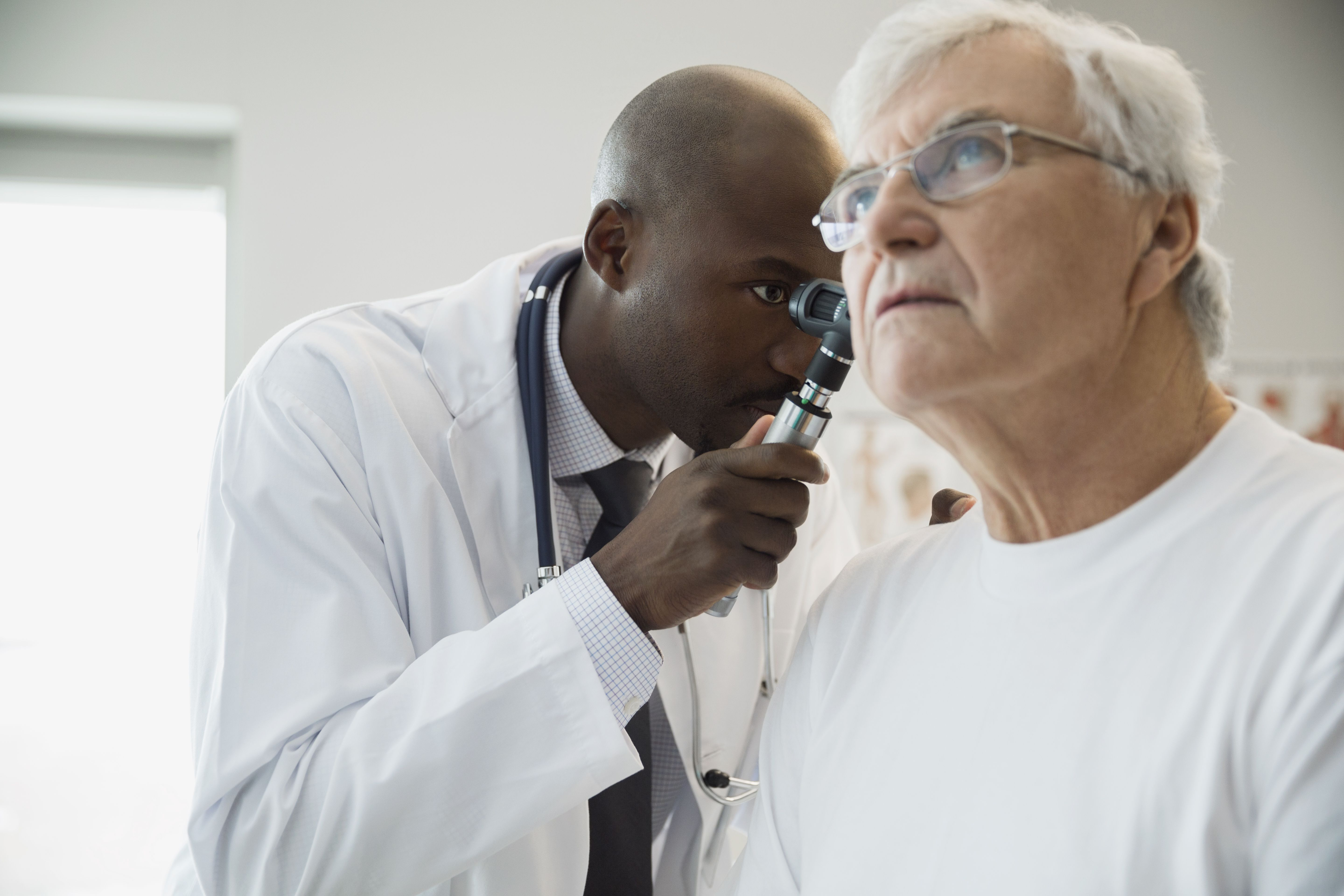 Doctor checking senior mans ear with otoscope