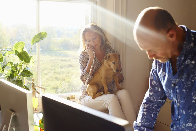 Woman and man in the same room together with their dog