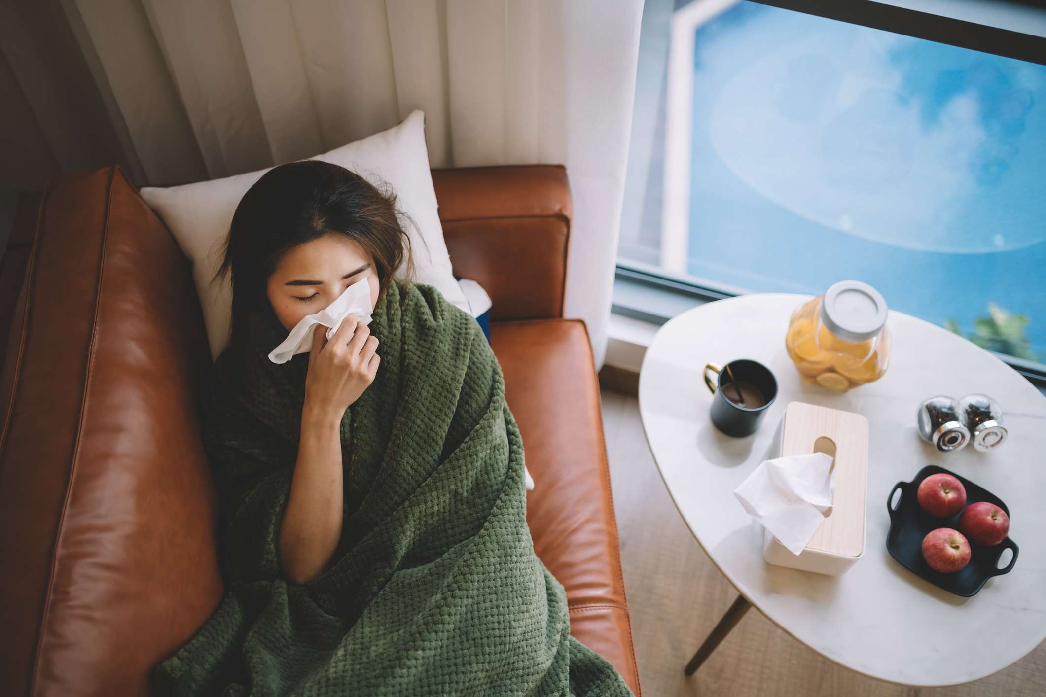 sick woman lying on couch blowing nose