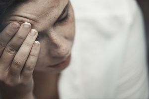 Woman suffering of headache and massaging forehead