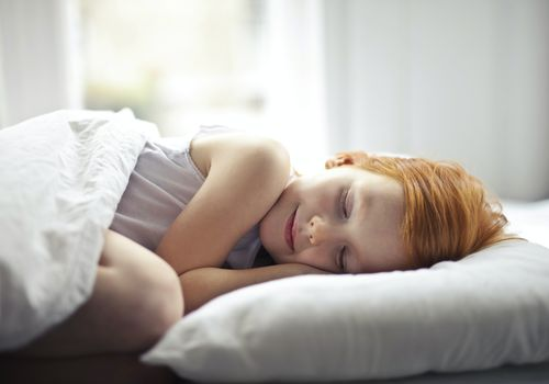 A young redheaded child sleeping peacefully.