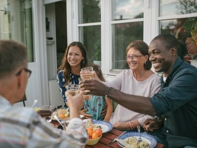 Happy multi-generation family toasting drinks at table during garden party
