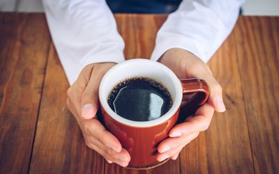Close up of a person's hands holding a cup of coffee.