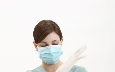 Nurse in surgical mask putting on rubber gloves, close-up