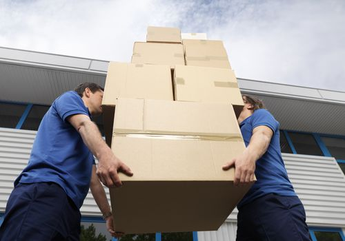 Two men lifting a stack of cardboard boxes