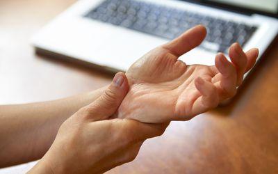 Woman massaging painful wrist at work repetitive strain injury