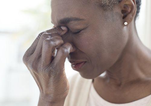 Woman pinching nose with headache