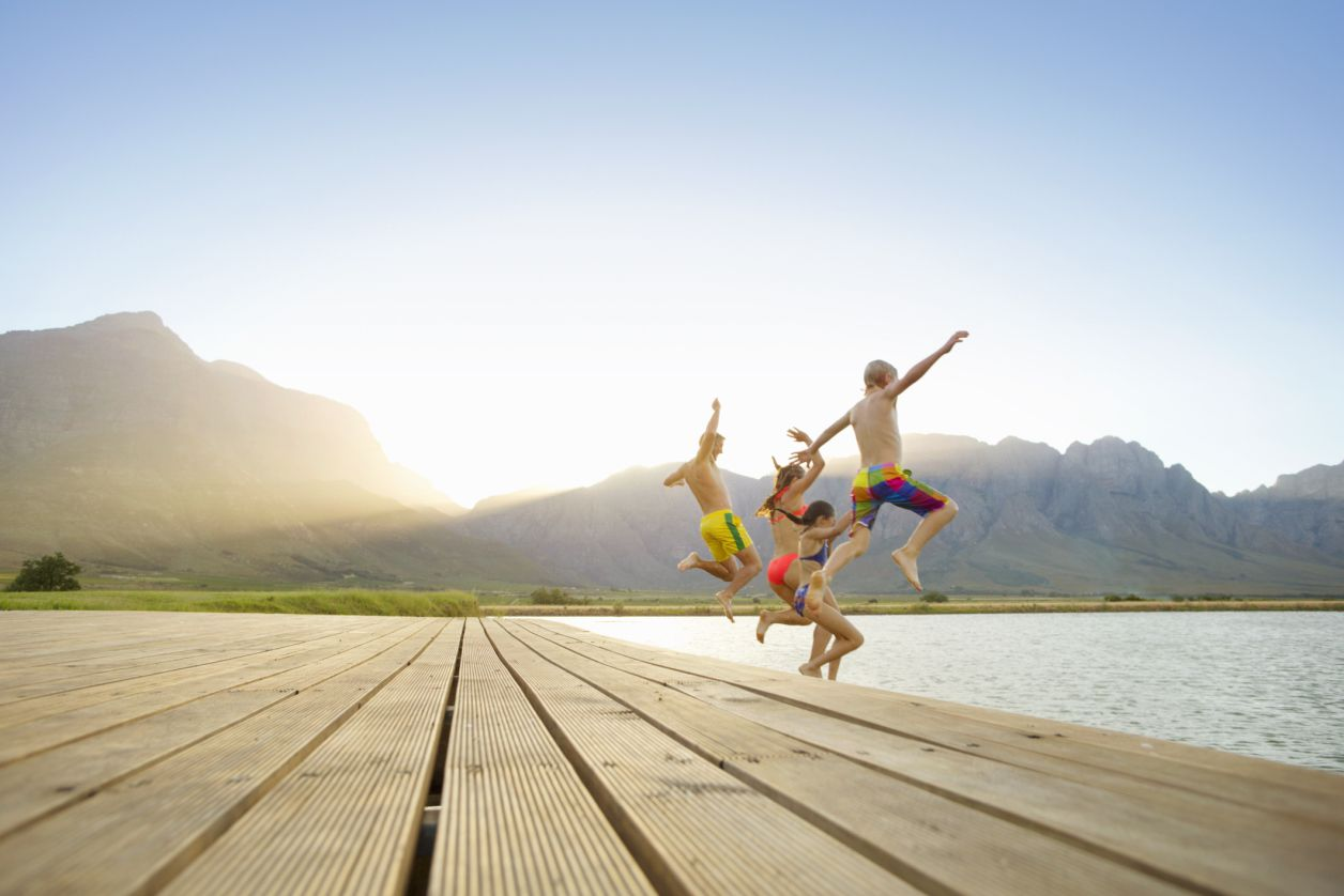 Photo of a family jumping off a dock into a lake