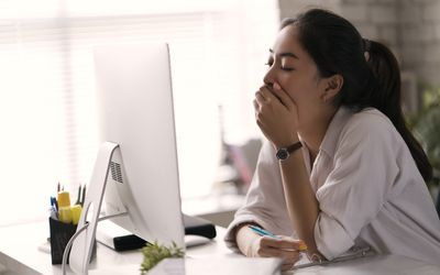 A woman yawning and tired at her office
