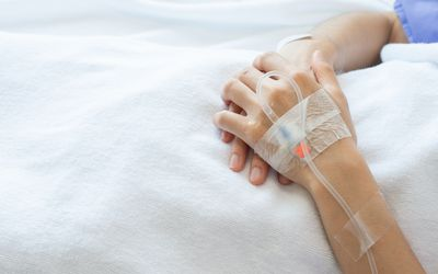 Cropped shot of patient hand receiving intravenous fluid directly into a blood vein.