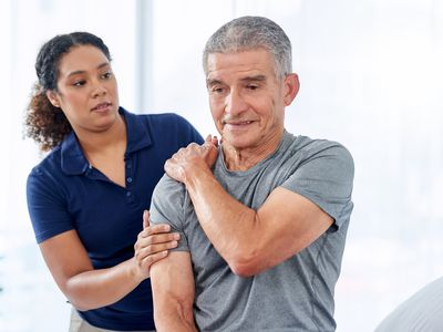 doctor standing behind a patient with hands on shoulder.