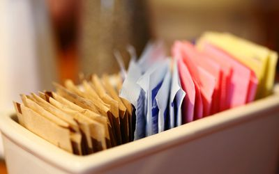 Close-Up Of Sugar And Sweetener Packets In Container At Cafe