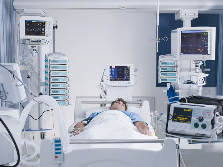 patient surrounded by monitors in intensive care
