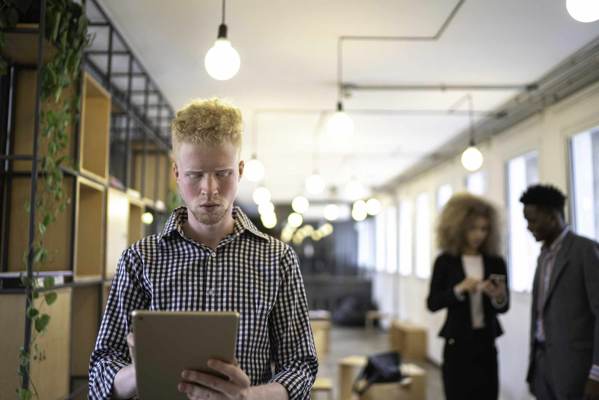 Man with albinism doing work on tablet in office setting