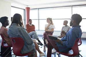 A group of young adults sit in chairs in a circle and listen to one woman talk
