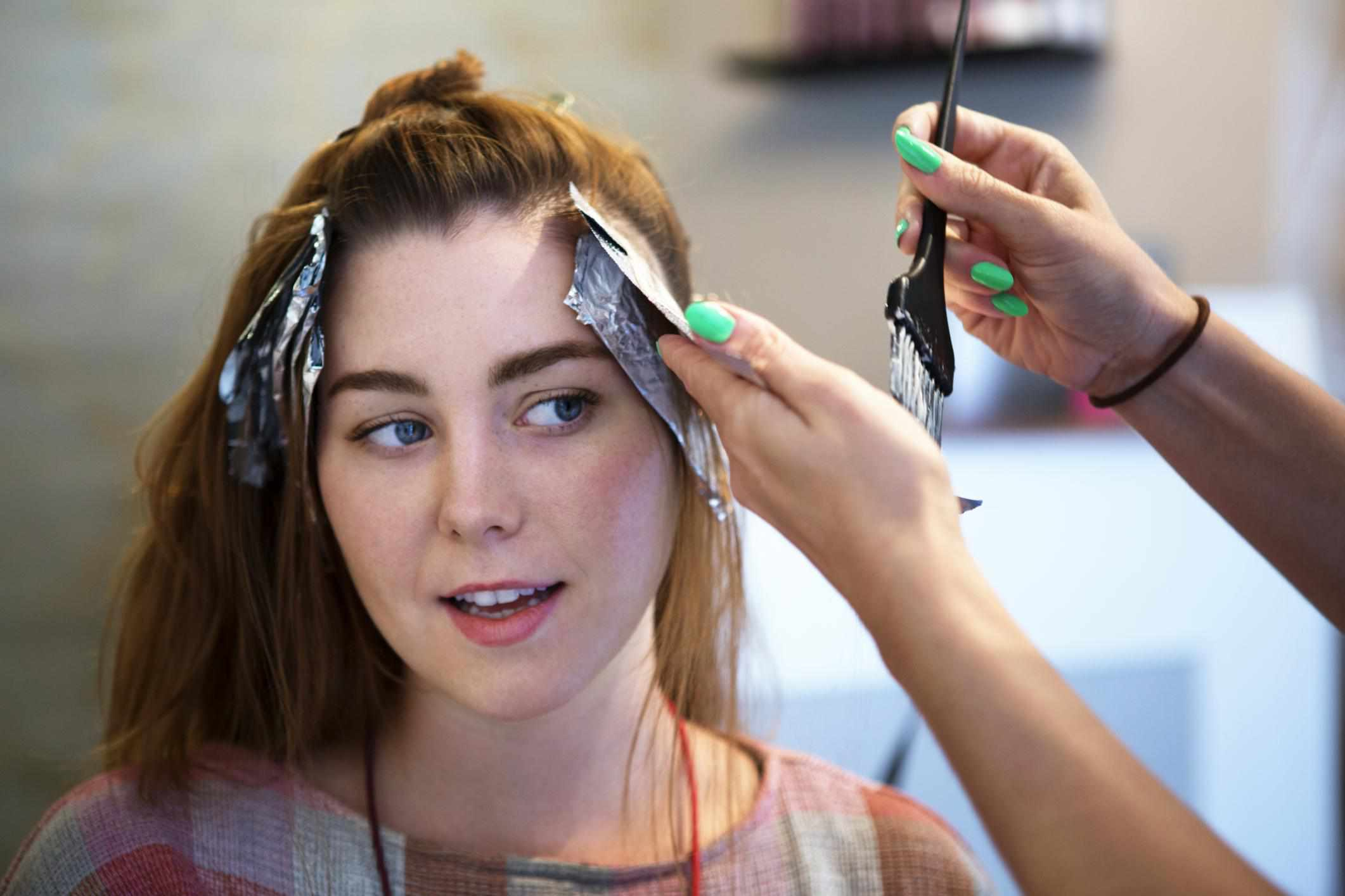 A woman getting her hair dyed with foils
