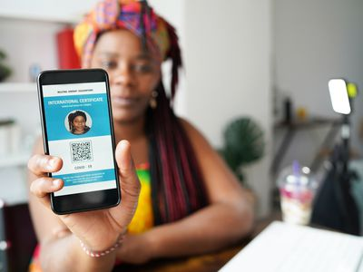 woman sitting at desk showing proof of vaccination on phone