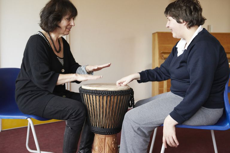 A music therapist and her pupil drum together