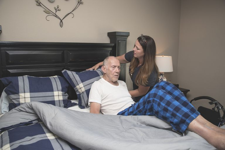 Woman positioning senior man in bed
