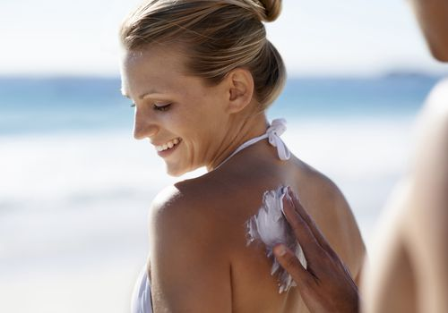 Man putting sun screen on smiling woman