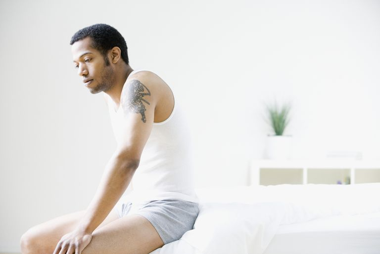 African American man sitting on edge of bed
