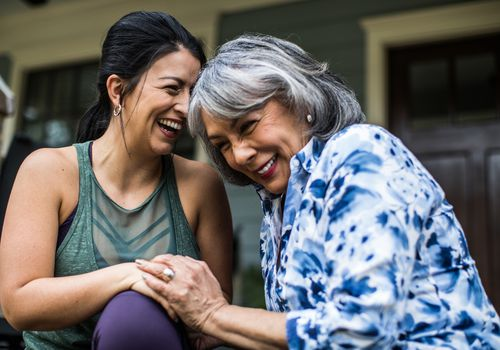 An older adult and an adult woman laughing together