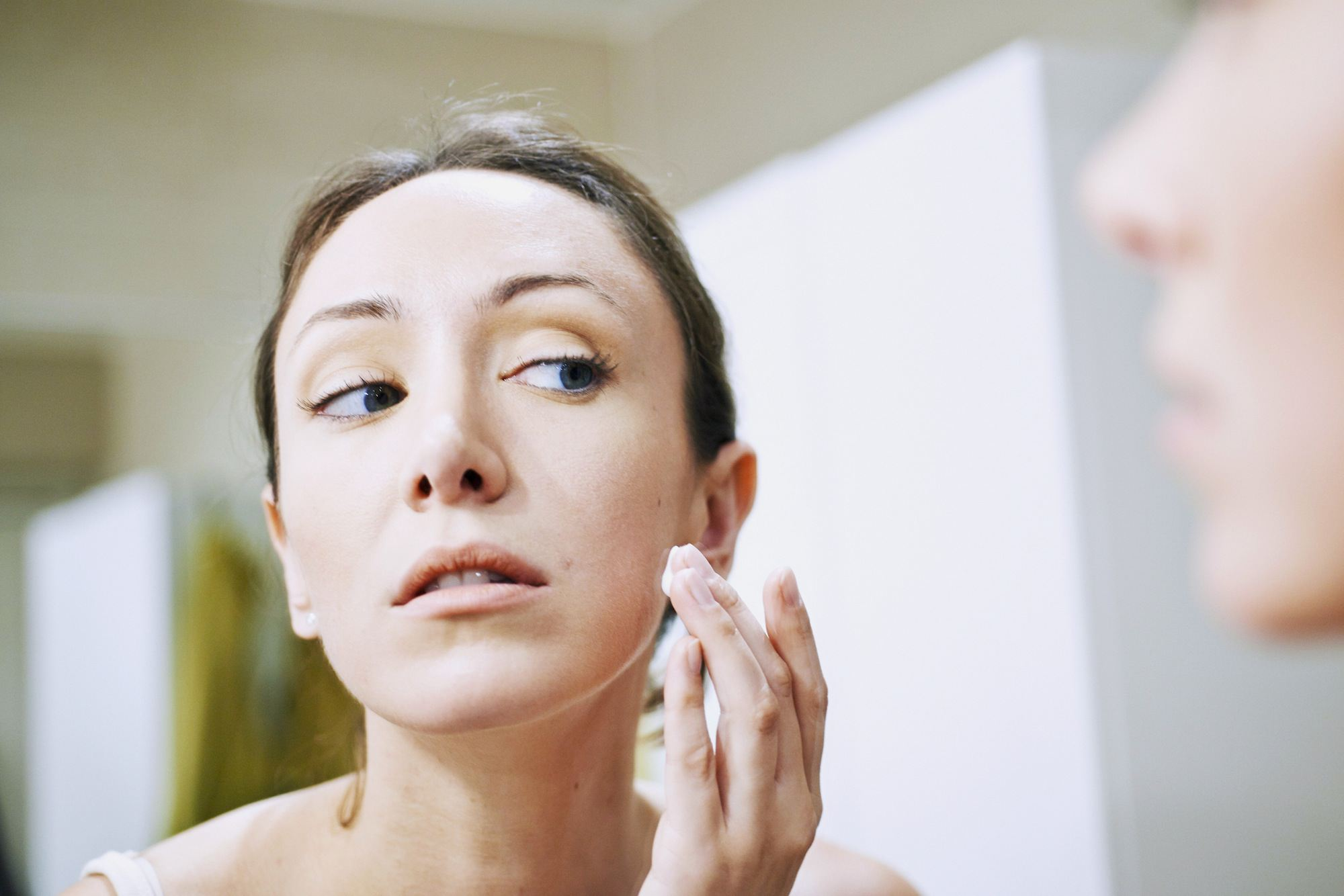 Woman applying cream on her face. France