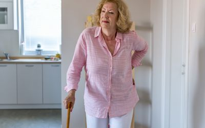 Woman walking with cane and holding lower back
