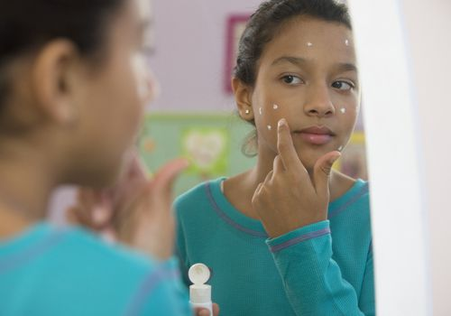 Young girl putting on acne cream