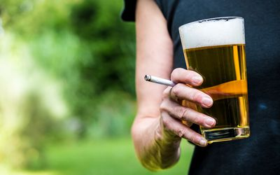 Drinking a beer and smoking cigarettes.