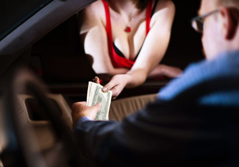 Man hands money to hooker through car window