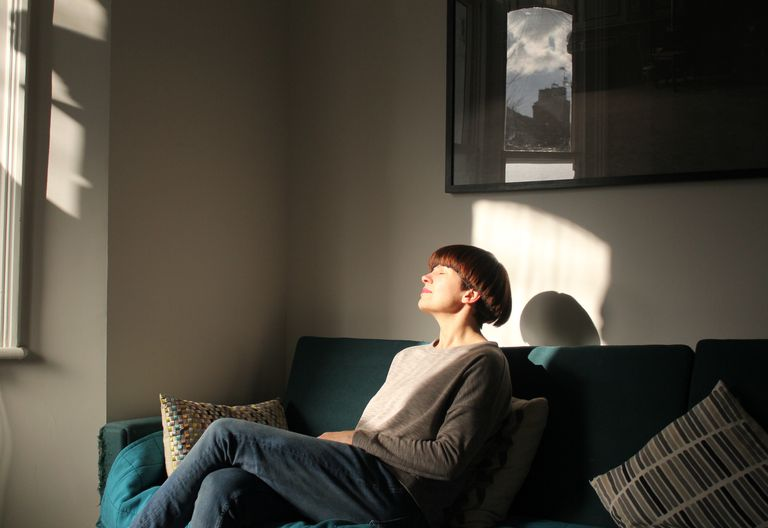 Woman sitting on the couch soaking up some sunshine