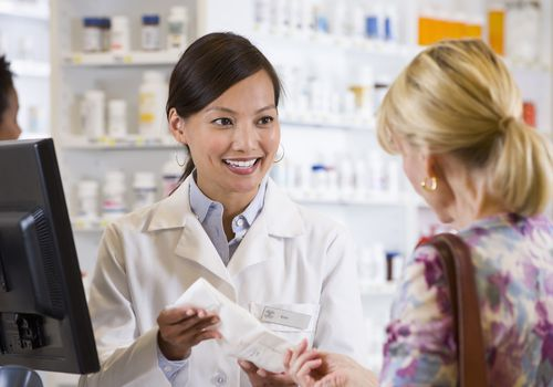 pharmacist handing prescription to a customer