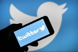 the Twitter logo is displayed on the screen of an iPhone in front of a computer screen displaying a Twitter logo