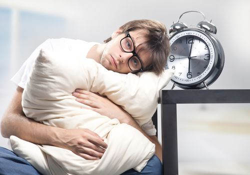 man looking sad next to giant alarm clock, holding a pillow