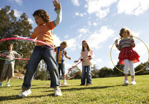 A picture of kids playing outdoors with hula hoops.