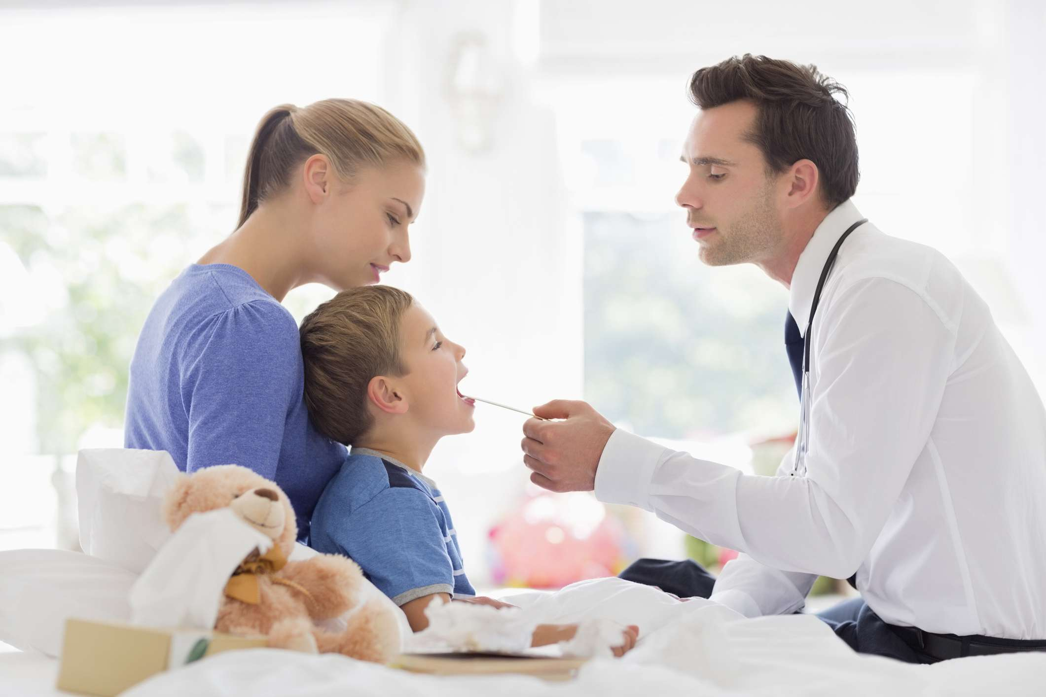 A doctor checking a child's throat