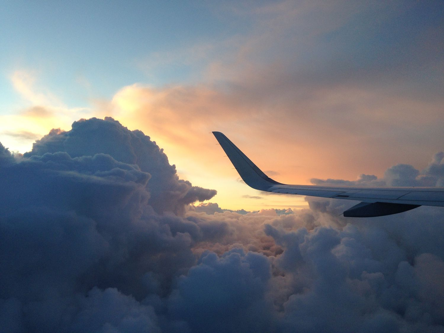 Cropped Image Of Airplane Flying Over Cloudy Sky At Sunset