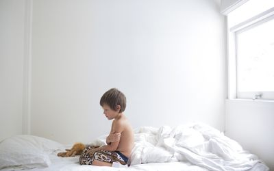 A young boy sitting on his bed