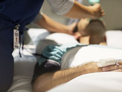 Doctor holding oxygen mask over male patients mouth in intensive care unit