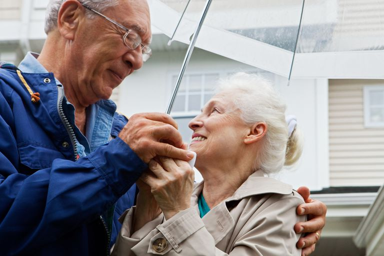 older couple smiling at each other under an umbrella