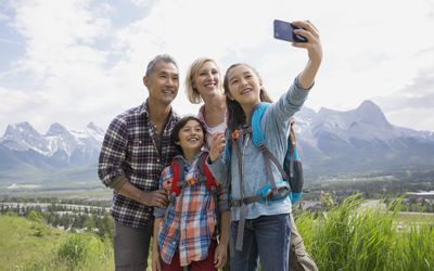 Family taking a selfie with a mountain range in the background