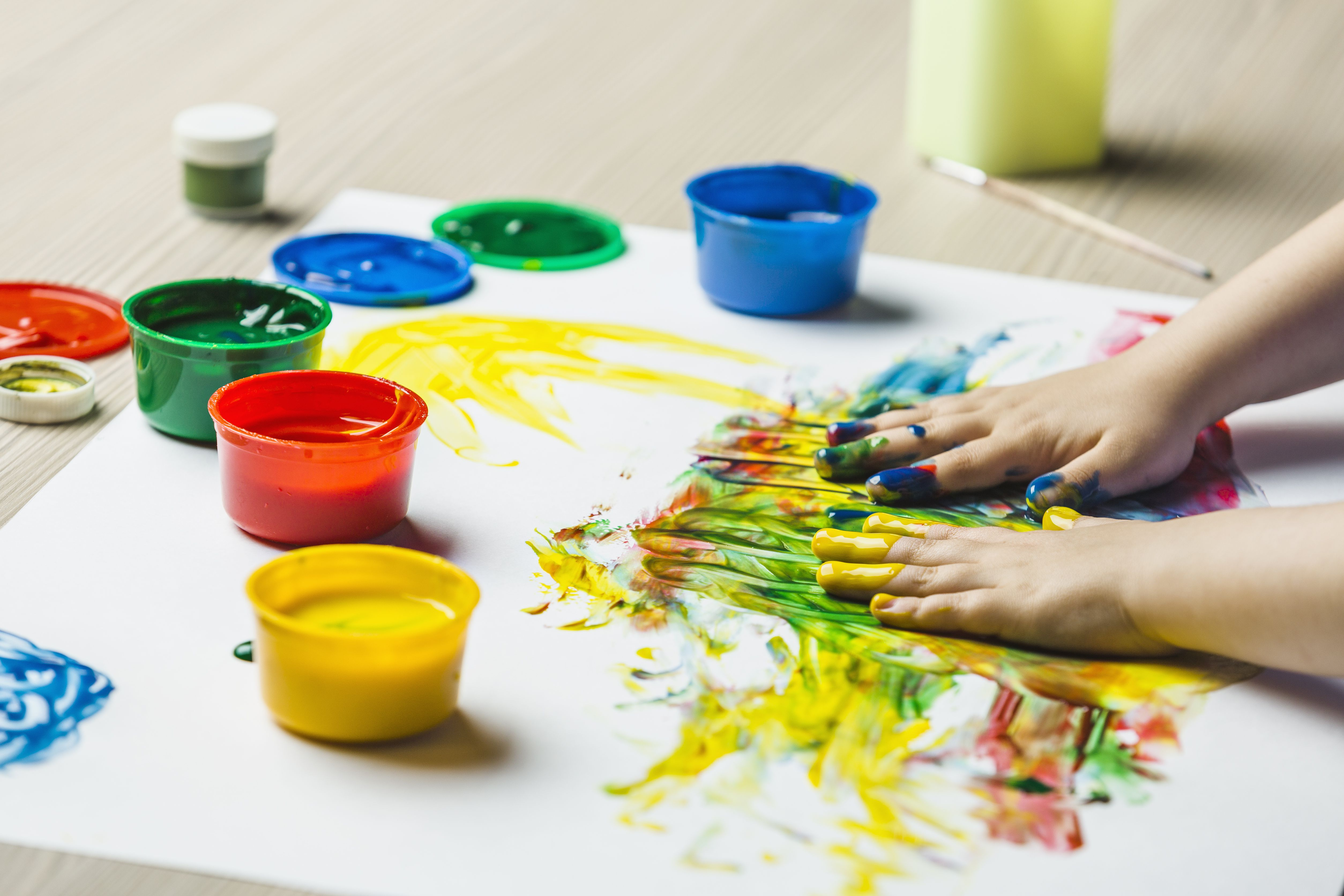 A child's hands finger painting on drawing paper