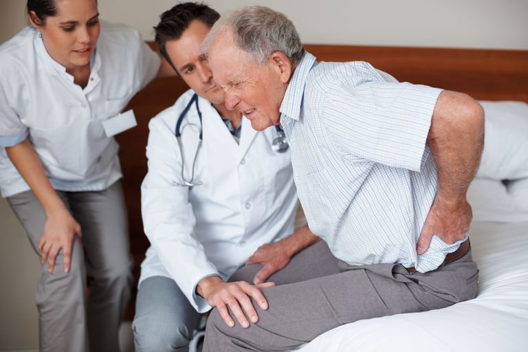 Elderly patient being assisted by two doctors