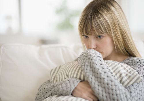 Anxious woman sitting on sofa