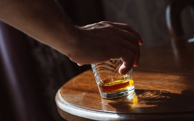 person placing glass of whisky on table