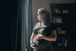 Pregnant woman in shadow wearing a face mask and looking out a window.