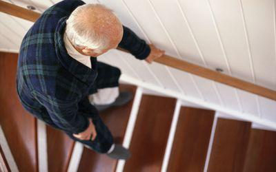 elderly man carefully descending stairs