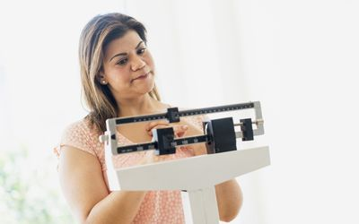 woman unhappy looking at a scale